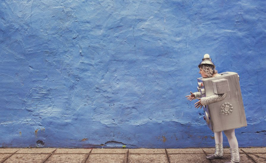 Old women dresses as a silver robot walking past a blue wall.