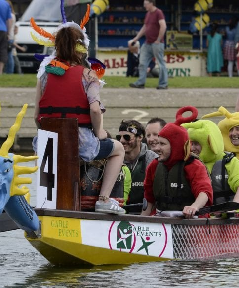 Team of people in a long boat dresses in telly-tubby costumes.