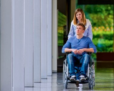 Man in wheelchair being pushed by a woman down a corridor.