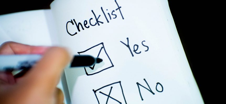 Checklist in a book with a marker being used to place a tick in the 'Yes' box.