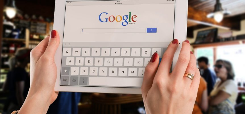 Tablet computer being held up with Google's website loaded.